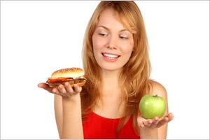 Žena v jednej ruke s jablkom a v druhej s hamburgerom
