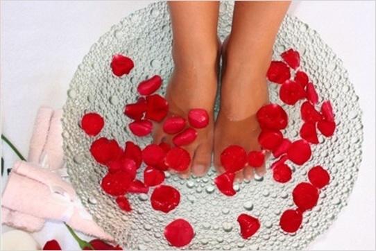 Nohy ponorené vo vode s lupeňami ruží