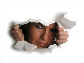 Žena pozerajúca cez roztrhnutý papier