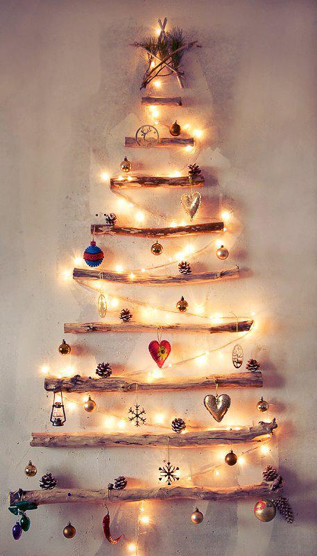 Jednoduchý vianočný stromček z konárov nalepený na stene