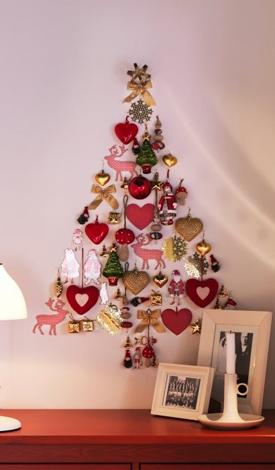 Malý vianočný stromček na stene vyrobený z vianočných ozdôb