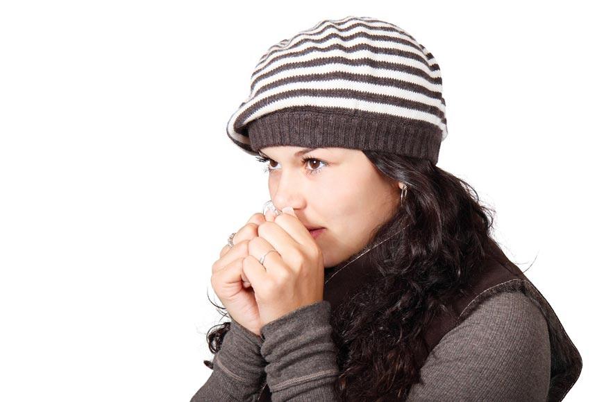 Žena v čiapke ohrievajúca si ruky