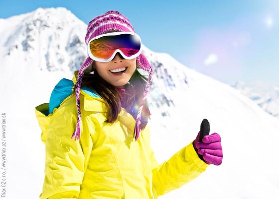 Žena v lyžiarskom oblečení so zdvihnutým palcom