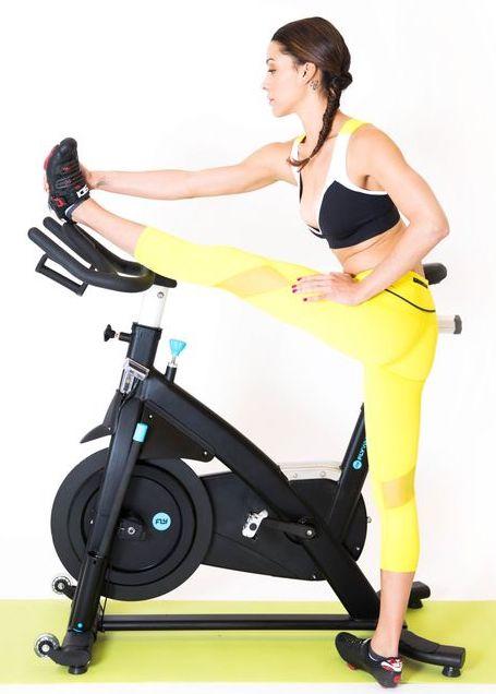 Žena strečuje nohu pred spinningom