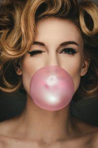 Žmurkajúca žena s nafúknutou žuvačkovou bubilnou