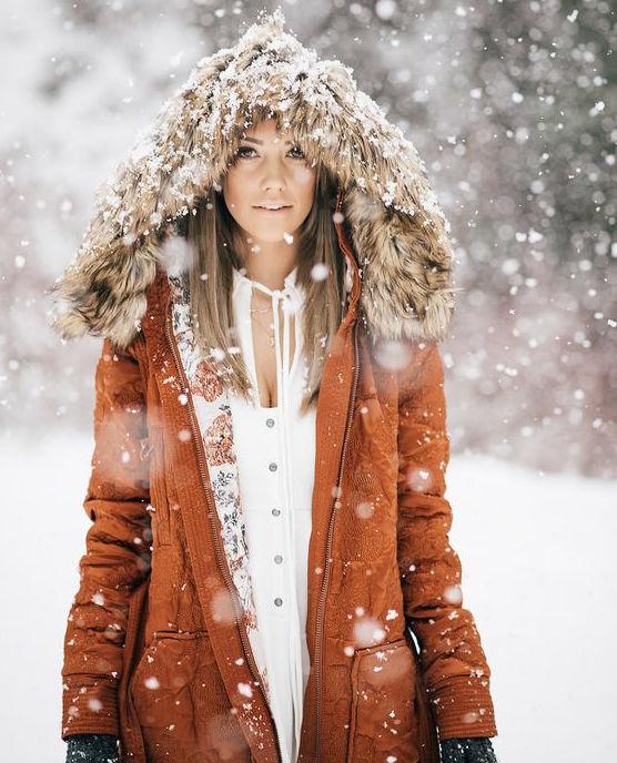 Žena s kapucňou na hlave na zasneženom svahu.