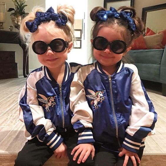 Dve krásne malé dievčatá v rovnakých bundách a mašličkách na hlave