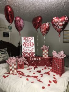 valentinska postel vyzdobena ruzami a srdcovymi balonmi